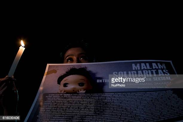 Photo taken in Jakarta Indonesia on 13 May 2016 show a young girl hold a candle with posters of solidarity to YY a child that being killed from gang...