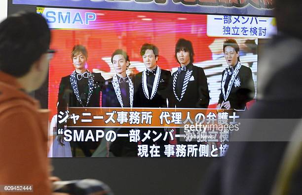 Photo taken in January 2016 shows pedestrians in Tokyo watching news that pop group SMAP is on the verge of breaking up SMAP is scheduled to release...