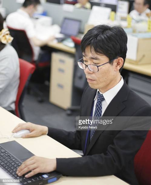 Photo taken in June 2017 in Tokyo's Shibuya Ward shows a man with a schizophrenic condition Kazuaki Hagiwara working as a backoffice section chief at...