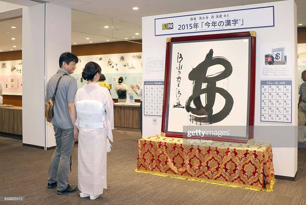 Photo taken in the western Japan city of Kyoto shows visitors looking at a calligraphy of the kanji character 'an,' meaning safety or peace, which was chosen as a symbolic character of the year 2015, at the Japan Kanji Museum & Library on June 29, 2016, the day of its opening. The museum, launched by the Japan Kanji Aptitude Testing Foundation, allows visitors to deepen their knowledge about the shape, sound and meaning of each Chinese character through interactive exhibitions.