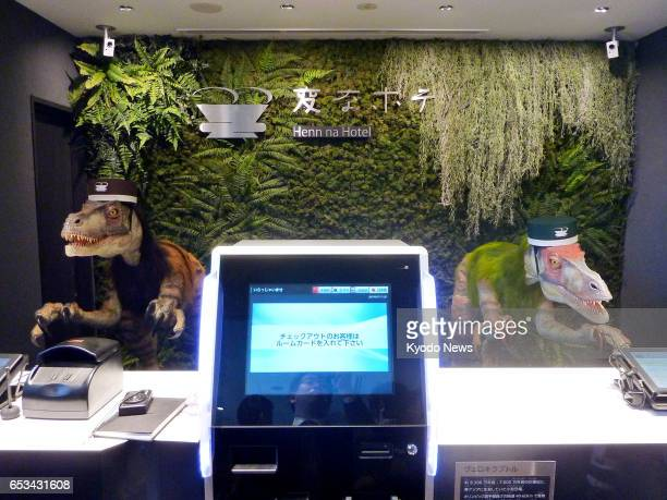 Photo taken March 15 shows the front desk of a hotel near Tokyo Disneyland operated by major travel agency HIS Co Two dinosaur robots welcome clients...