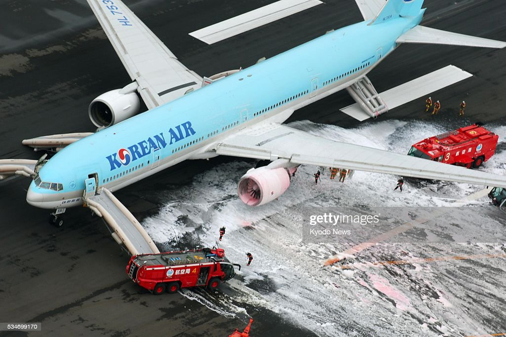 Photo taken May 27, 2016, from a Kyodo News helicopter shows a Korean Air aircraft with white smoke pouring from its left engine at Tokyo's Haneda airport. No injuries have been reported so far as a result of the accident when the plane bound for Seoul aborted takeoff.