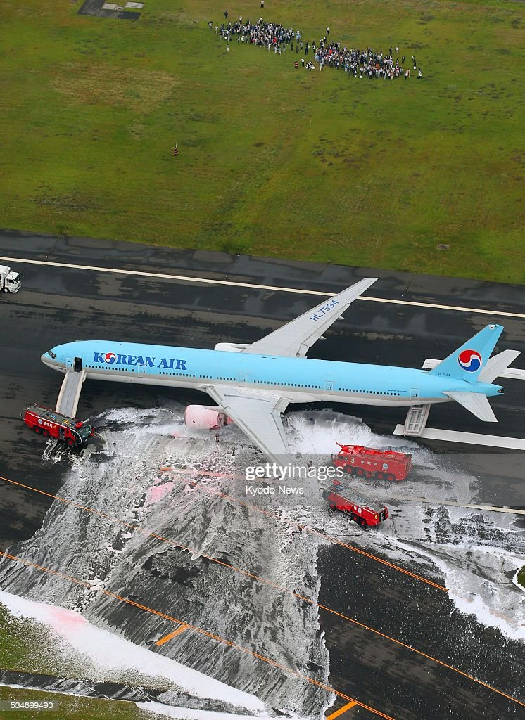 Photo taken May 27, 2016, from a Kyodo News helicopter shows a Korean Air jet being doused with fire retardant foam after its left engine caught fire at Tokyo's Haneda airport. Evacuated passengers are seen above. Some passengers said they felt ill after being evacuated, although no injuries have been reported as a result of the incident which forced the plane bound for Seoul to abort its takeoff.