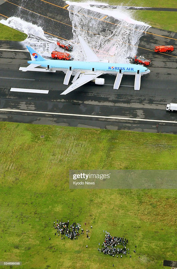 Photo taken May 27, 2016, from a Kyodo News helicopter shows a Korean Air jet being doused with fire retardant foam after its left engine caught fire at Tokyo's Haneda airport. Evacuated passengers are seen below. Some passengers said they felt ill after being evacuated, although no injuries have been reported as a result of the incident which forced the plane bound for Seoul to abort its takeoff.
