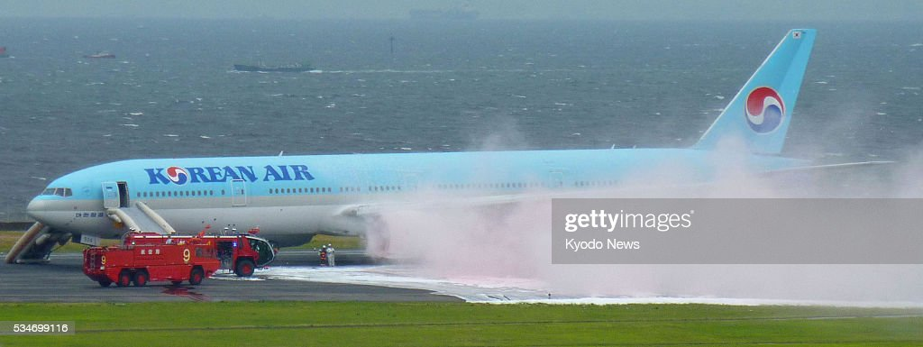 Photo taken May 27, 2016, shows a Korean Air aircraft with white smoke pouring from its left engine at Tokyo's Haneda airport. No injuries have been reported so far as a result of the accident when the plane bound for Seoul aborted takeoff.