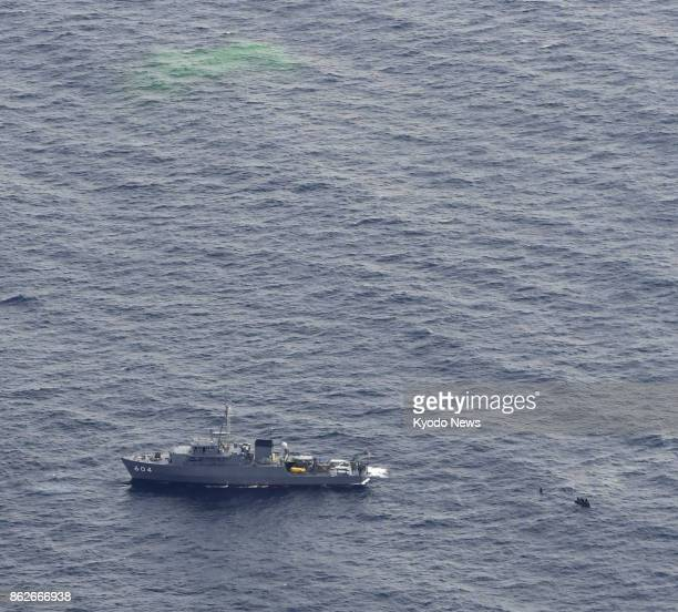 Photo taken Oct 18 from a Kyodo News helicopter shows a Maritime SelfDefense Force vessel searching for four crew members who went missing in an ASDF...