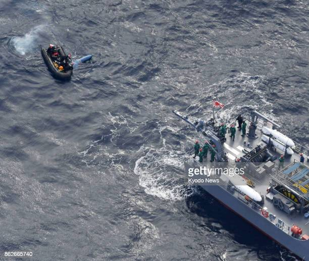 Photo taken Oct 18 from a Kyodo News helicopter shows a search operation by Japan's SelfDefense Forces for four crew members who went missing in an...