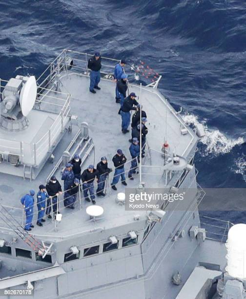 Photo taken Oct 18 from a Kyodo News helicopter shows SelfDefense Forces personnel on an escort ship searching for four crew members who went missing...