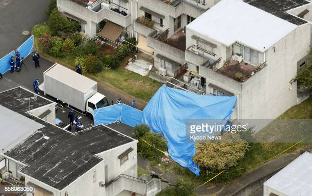 Photo taken Oct 6 from a Kyodo News helicopter shows police officers investigating the scene of an apartment fire that killed six people in Hitachi...