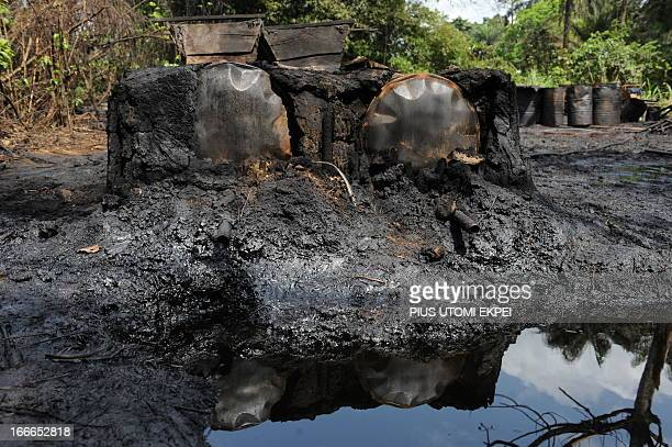 A photo taken on April 11 2013 shows a locally built dump for crude oil waste from an illegal oil refinery operated by oil thieves in Bayelsa State...