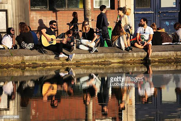 photo taken on april 13 2015 shows people enjoying afterwork along the Saint Martin canal at the sunset in Paris AFP PHOTO / LUDOVIC MARIN