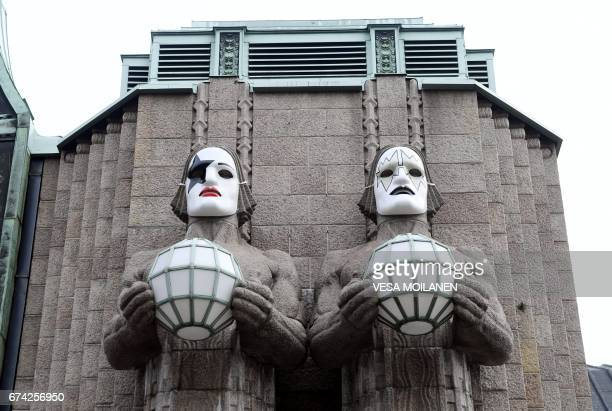 A photo taken on April 28 2017 shows statues with painting masks in tribute to the members of the KISS rock band at the Helsinki Central Station VR...