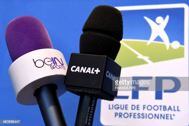Photo taken on April 4 2014 in Paris shows microphones of French television channel Canal and Qatari station BeIn Sports The French Ligue de Football...