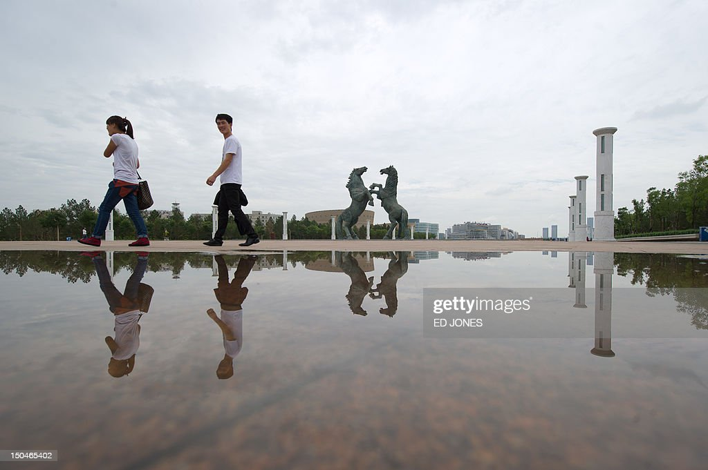 A photo taken on August 18, 2012 shows a couple reflected in a puddle as they walk through Genghis Khan Plaza, in the inner Mongolian city of Ordos. Miss China won the coveted title of Miss World on August 18, triumphing on home soil during a glitzy final held in a mining city on the edge of the Gobi desert. The city has grown rich over the past decade on the back of a coal mining boom that has transformed it from a sandstorm-afflicted backwater into one of the wealthiest places in China. The boom triggered a frenzy of building in the city, but the local government has struggled to fill the vast tower blocks that sprung up, earning it the title of China's biggest ghost town. AFP PHOTO / Ed Jones