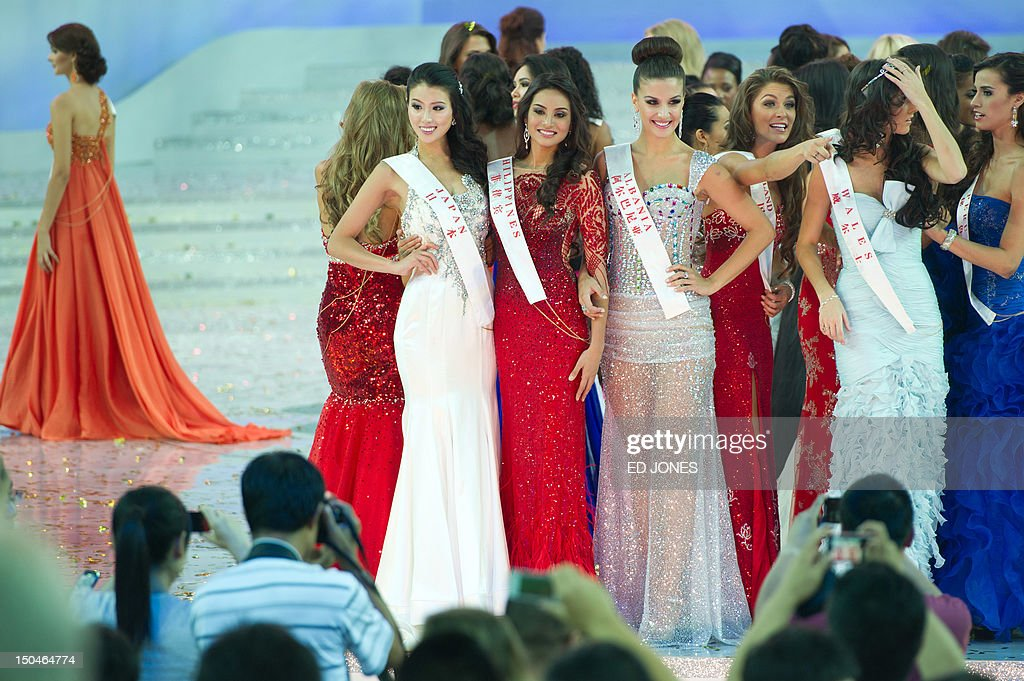 A photo taken on August 18, 2012 shows Miss Japan Nozomi Igarashi (L), Miss Philippines Quenerich Rehman (C), and Miss Albania Floriana Garo (R) posing for photos following the Miss World final ceremony at the Dongsheng stadium in the inner Mongolian city of Ordos. China's Yu Wenxia of China defeated more than 100 other hopefuls at the glittering ceremony held in the Chinese mining city of Ordos, on the edge of the Gobi desert. AFP PHOTO / Ed Jones