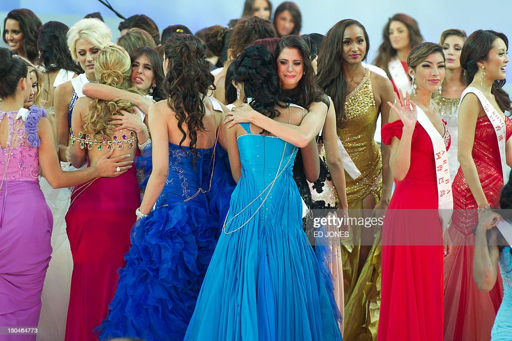 A photo taken on August 18, 2012 shows Miss World 2012 contestants as they console each other following the pageant's final ceremony at the Dongsheng stadium in the inner Mongolian city of Ordos. China's Yu Wenxia of China defeated more than 100 other hopefuls at the glittering ceremony held in the Chinese mining city of Ordos, on the edge of the Gobi desert. AFP PHOTO / Ed Jones