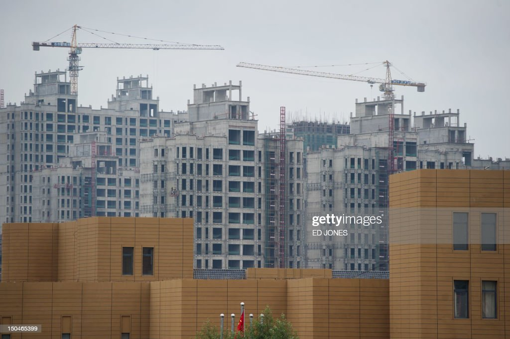 A photo taken on August 18, 2012 shows ongoing construction in the inner Mongolian city of Ordos. Miss China won the coveted title of Miss World on August 18, triumphing on home soil during a glitzy final held in a mining city on the edge of the Gobi desert. The city has grown rich over the past decade on the back of a coal mining boom that has transformed it from a sandstorm-afflicted backwater into one of the wealthiest places in China. The boom triggered a frenzy of building in the city, but the local government has struggled to fill the vast tower blocks that sprung up, earning it the title of China's biggest ghost town. AFP PHOTO / Ed Jones