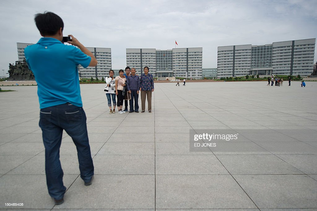 A photo taken on August 18, 2012 shows people posing before government buildings in Genghis Khan Plaza, in the inner Mongolian city of Ordos. Miss China won the coveted title of Miss World on August 18, triumphing on home soil during a glitzy final held in a mining city on the edge of the Gobi desert. The city has grown rich over the past decade on the back of a coal mining boom that has transformed it from a sandstorm-afflicted backwater into one of the wealthiest places in China. The boom triggered a frenzy of building in the city, but the local government has struggled to fill the vast tower blocks that sprung up, earning it the title of China's biggest ghost town. AFP PHOTO / Ed Jones