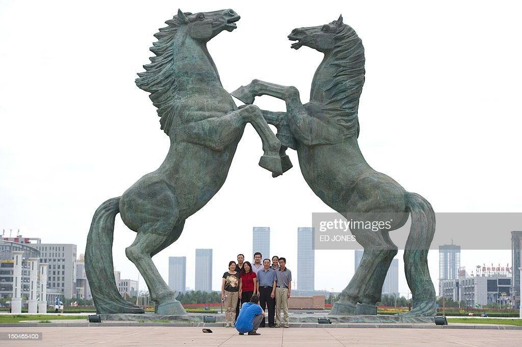 A photo taken on August 18, 2012 shows people posing beneath a statue in Genghis Khan Plaza, in the inner Mongolian city of Ordos. Miss China won the coveted title of Miss World on August 18, triumphing on home soil during a glitzy final held in a mining city on the edge of the Gobi desert. The city has grown rich over the past decade on the back of a coal mining boom that has transformed it from a sandstorm-afflicted backwater into one of the wealthiest places in China. The boom triggered a frenzy of building in the city, but the local government has struggled to fill the vast tower blocks that sprung up, earning it the title of China's biggest ghost town. AFP PHOTO / Ed Jones