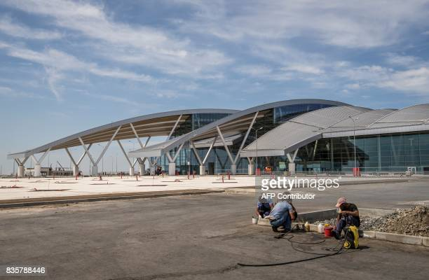 A photo taken on August 20 2017 shows workers adding the final touches to the newly built 'Platov' airport outside of the Southern Russian city of...