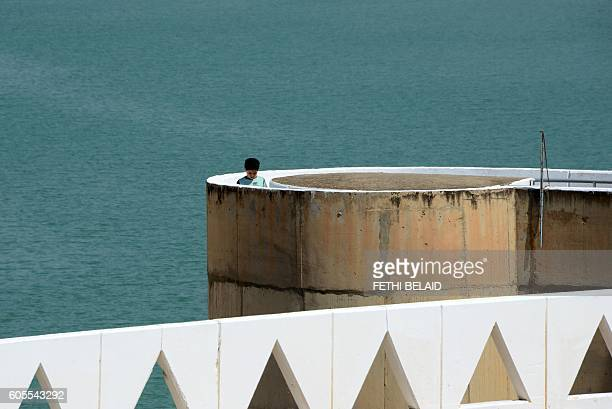 A photo taken on August 21 2016 shows a boy walking along the Sidi Salem dam near Testour in Tunisia's northwest Beja region which has particularly...