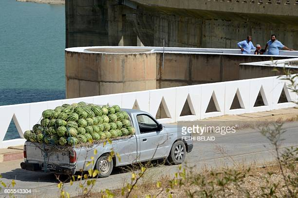 A photo taken on August 21 2016 shows a truck carrying watermelons driving along the Sidi Salem dam near Testour in Tunisia's northwest Beja region...