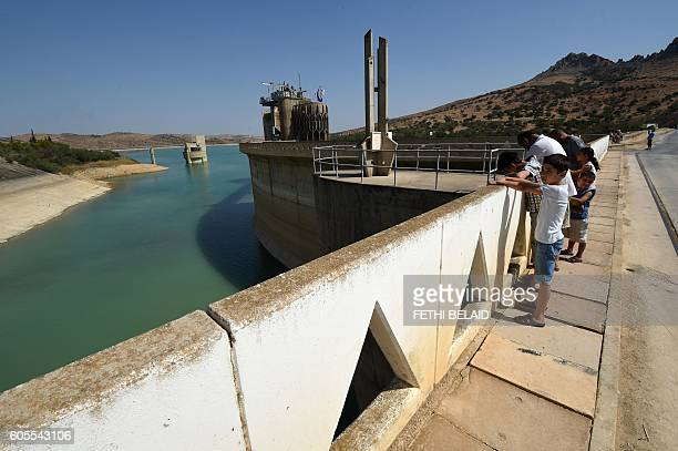 A photo taken on August 21 2016 shows Tunisians looking at the Sidi Salem dam near Testour in Tunisia's northwest Beja region which has particularly...