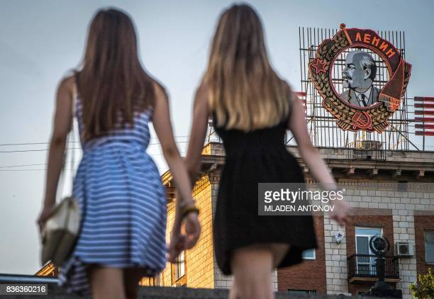 TOPSHOT A photo taken on August 21 2017 shows girls passing in front of a building with a display of the Soviet state founder Vladimir Lenin Order in...