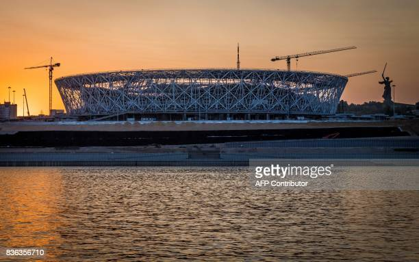 TOPSHOT A photo taken on August 21 2017 shows the Volgograd Arena stadium and the statue of Mother Homeland at the Mamayev Kurgan World War Two...