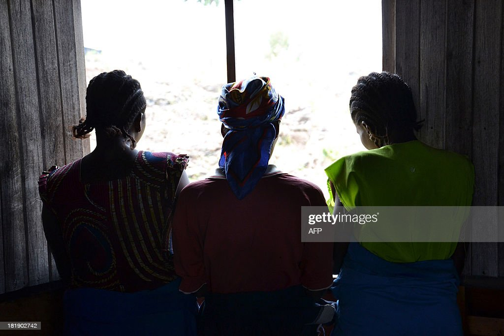 A photo taken on August 22 2013 shows three women who have been trained to make bricks out of wood sawdust paper and water posing in the Mugunga III...