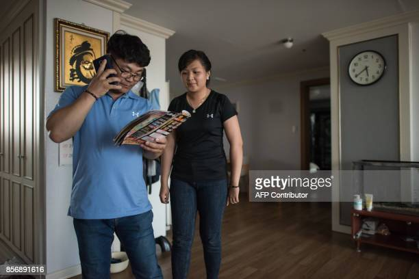 A photo taken on August 23 2017 shows Huynh Thi Thai Muoi of Vietnam and husband Kim KyeongBok ordering a food delivery in their apartment in Gwangju...
