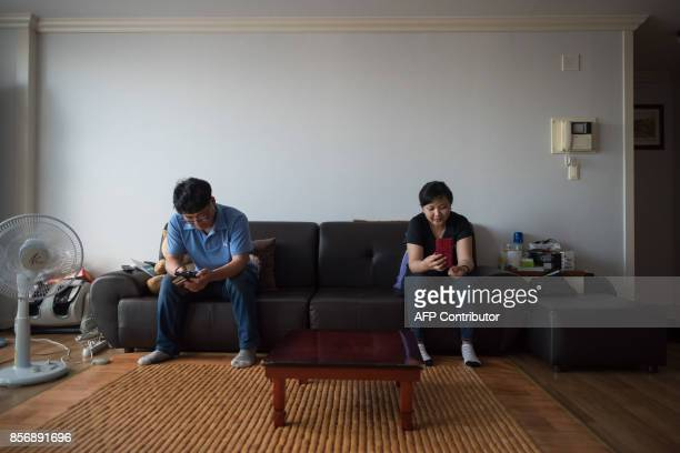 A photo taken on August 23 2017 shows Huynh Thi Thai Muoi of Vietnam and husband Kim KyeongBok of South Korea looking at mobile phones in their...