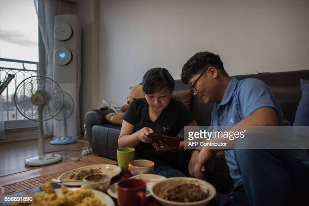 A photo taken on August 23 2017 shows Huynh Thi Thai Muoi of Vietnam and husband Kim KyeongBok of South Korea looking at a mobile phone in their...