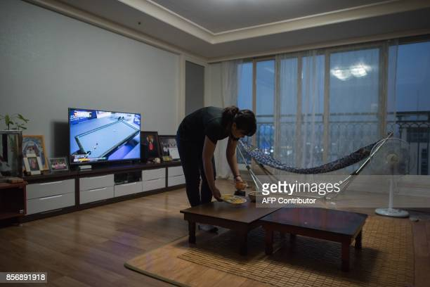 A photo taken on August 23 2017 shows Huynh Thi Thai Muoi of Vietnam clearing food from a table in the apartment she shares with husband Kim...