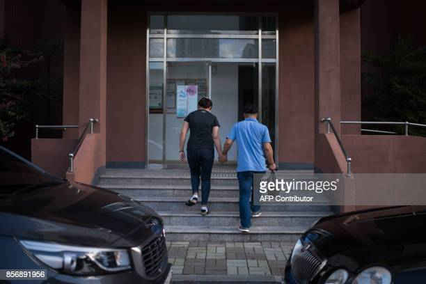 A photo taken on August 23 2017 shows Huynh Thi Thai Muoi of Vietnam and husband Kim KyeongBok of South Korea entering their apartment building in...