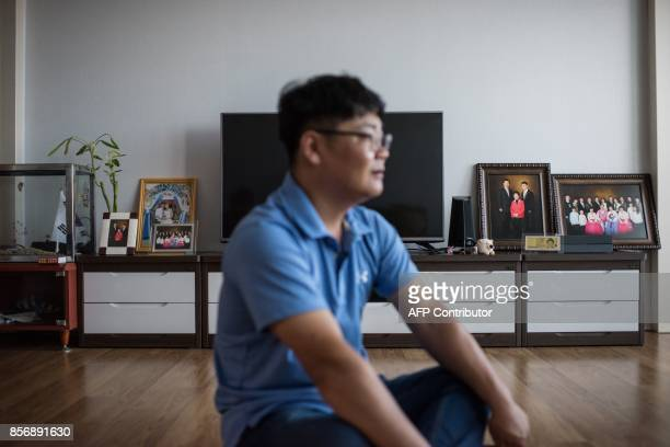 A photo taken on August 23 2017 shows Kim KyeongBok sitting in the apartment he shares with his wife Huynh Thi Thai Muoi in Gwangju There are some...