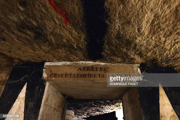 Photo taken on August 7 2014 at the Catacombs of Paris shows the entrance to the ossuary Sign Stop This is the empire of death These underground...