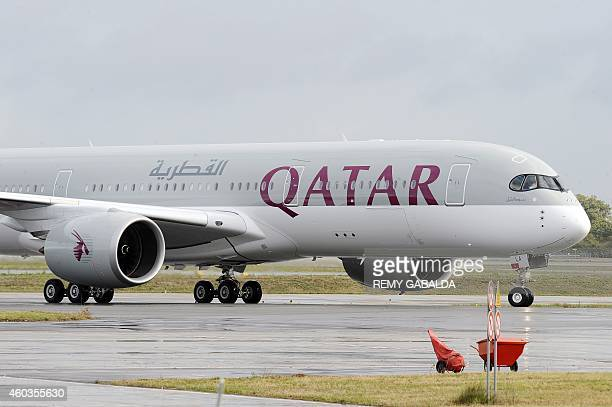 A photo taken on December 11 2014 shows the first Airbus A350 bearing the Qatar airline company logo on the tarmac of Toulouse Blagnac airport...