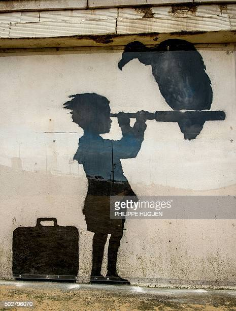 A photo taken on December 29 2015 shows an art piece protected by a plexiglass pane by British artist Banksy representing a child with a suitcase...