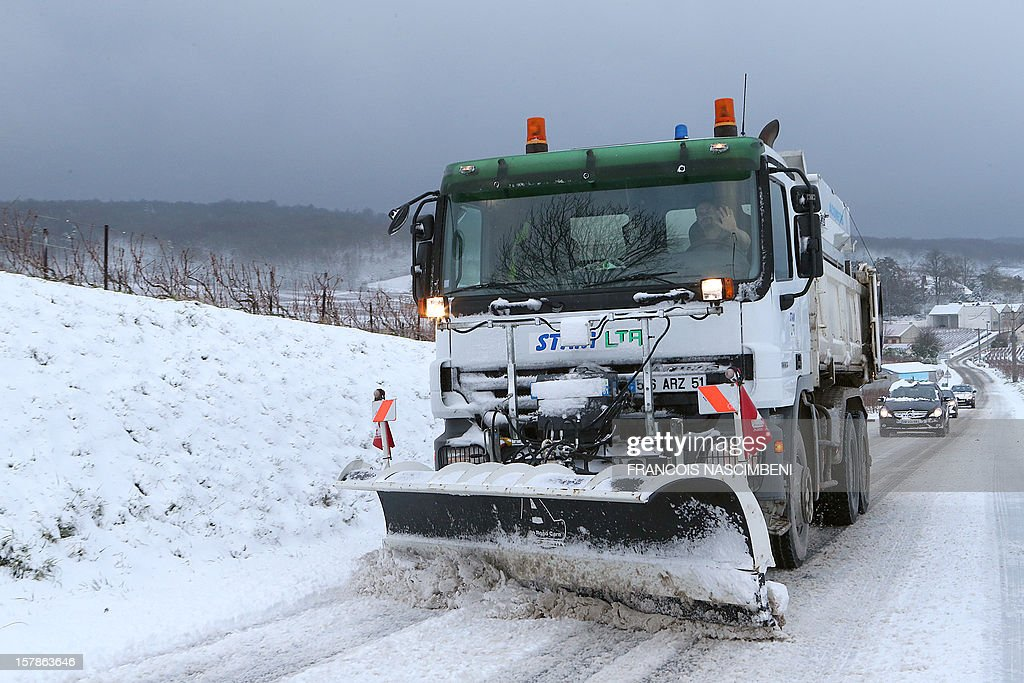 Photo taken on December 7, 2012 shows a snow plough cleaning a road in the snow-covered Champagne region of Reims, northeastern France, after an overnight fall.