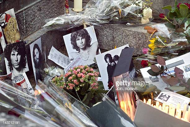 Photo taken on December 8 2003 in Paris shows photographs and flowers on the grave of Jim Morrison at Pere Lachaise cemetery It will be 40 years on...