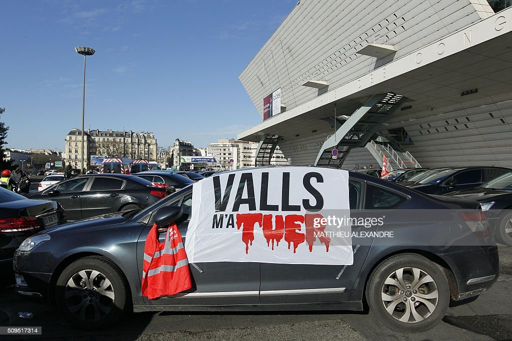 A photo taken on February 11, 2016 shows a banner on a windshield reading 'Valls killed me' as drivers of Uber and other ride-hailing companies, known in France as 'voitures de tourisme avec chauffeur' (VTC), a class of companies that allow passengers to book rides with independent professional chauffeurs, gather at Porte Maillot in Paris to defend jobs they believe are threatened by measures the government recently announced in favor of taxis. / AFP / MATTHIEU ALEXANDRE