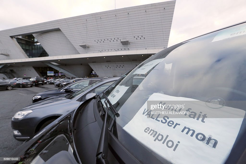 A photo taken on February 11, 2016 shows a placard seen through a windshield reading 'Manu toys my job' as Drivers of Uber and other ride-hailing companies, known in France as 'voitures de tourisme avec chauffeur' (VTC), a class of companies that allow passengers to book rides with independent professional chauffeurs, gather at Porte Maillot in Paris to defend jobs they believe are threatened by measures the government recently announced in favor of taxis. / AFP / MATTHIEU ALEXANDRE