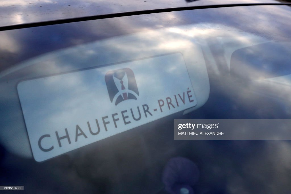 A photo taken on February 11, 2016 shows a logo through a windshield reading 'Private Driver' as Drivers of Uber and other ride-hailing companies, known in France as 'voitures de tourisme avec chauffeur' (VTC), a class of companies that allow passengers to book rides with independent professional chauffeurs, gather at Porte Maillot in Paris to defend jobs they believe are threatened by measures the government recently announced in favor of taxis. / AFP / MATTHIEU ALEXANDRE