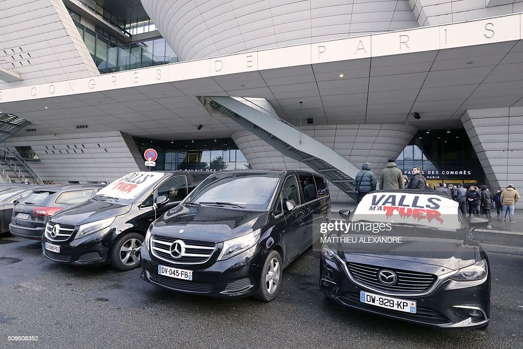 A photo taken on February 11, 2016 shows banners on windshields reading 'Valls killed me' as Drivers of Uber and other ride-hailing companies, known in France as 'voitures de tourisme avec chauffeur' (VTC), a class of companies that allow passengers to book rides with independent professional chauffeurs, gather at Porte Maillot in Paris to defend jobs they believe are threatened by measures the government recently announced in favor of taxis. / AFP / MATTHIEU ALEXANDRE