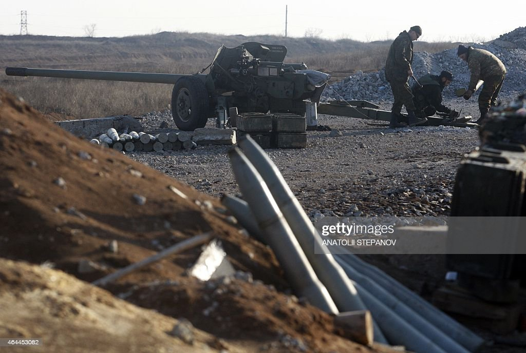 A photo taken on February 25 2015 shows Ukrainian soldiers repairing artillery at a position of the Ukrainian forces near the village of Pervomayske...