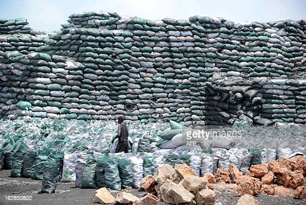 Photo taken on February 27 2013 shows a Somali worker filling a sack with charcoal as they are prepared for transportation near the Kismayo seaport...
