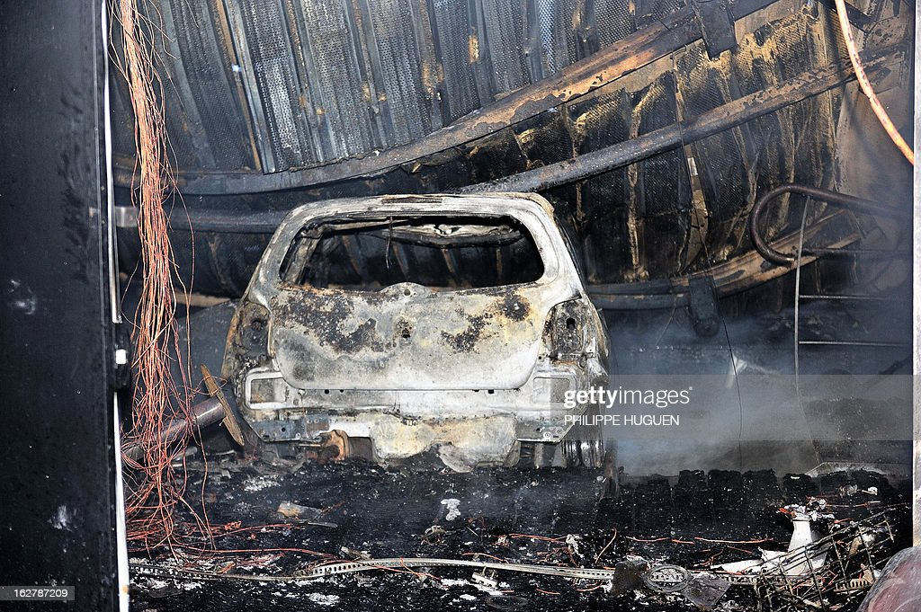 A photo taken on February 27, 2013 shows the car that was used to smash the door of the nightclub 'La Fabrik' in Villeneuve d'Ascq before a fire was set. AFP PHOTO PHILIPPE HUGUEN