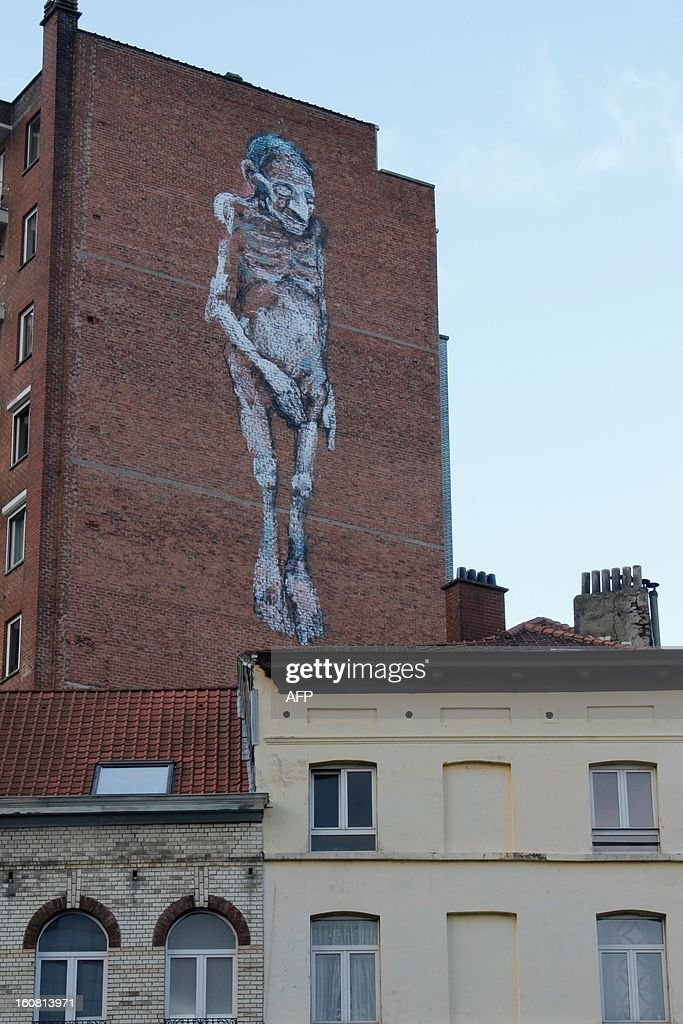 A photo taken on February 6, 2013 shows a giant graffito, representing an elderly man, that appeared overnight on a the wall of a building on the Hallepoortlaan / Avenue de la Porte de Hal in Brussels. The work is thought to be that of graffiti artist Bonom, whose real name is Vincent Glowinski, but he denies any involvement.