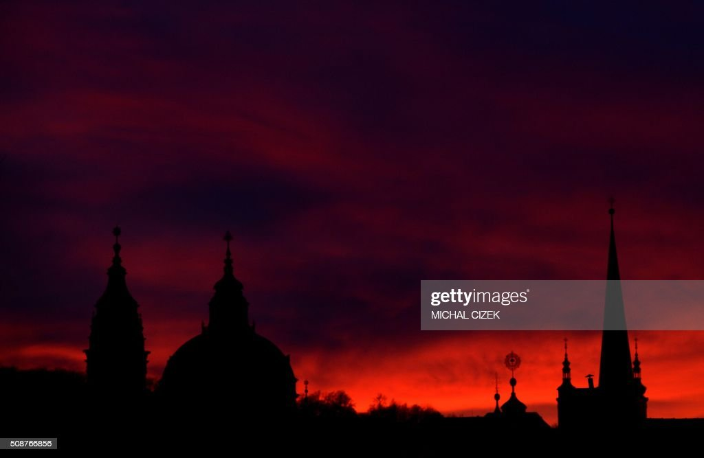Photo taken on February 6, 2016 in Prague shows St Nicholas church (l) during the sunset. / AFP / Michal Cizek